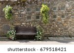 Small photo of Lonely bench near the old castle and old stone wall with the beautiful flowers decoration in village Yvoire, shore the Leman lake
