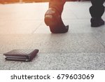 Small photo of businessman had lost leather wallet with money on the street. Close-up of wallet lying on the sidewalk in during the trip to work.