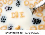 The word DIE spelled out of letter shaped cereal pieces floating in a milk filled cereal bowl. - stock photo