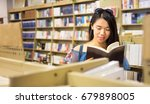 asian girl reading a book in a... | Shutterstock . vector #679898005
