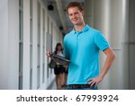 A handsome smiling college student holding a laptop standing in corridor of modern campus.  20s tall English male caucasian in blue collared shirt looking at camera - stock photo