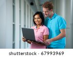 Two diverse students standing close sharing laptop in hallway inside university building. Female Asian Thai Chinese model smiling looking at camera. Male British caucasian looking over shoulder - stock photo