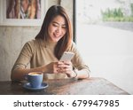 Small photo of Young Asian beautiful woman using smart phone for business, online shopping, transfer money, financial, internet banking. in coffee shop cafe over blurred background.