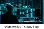 Team of Internationally Wanted Hackers Teem Organizing Advanced Malware Attack on Corporate Servers. Hacker is Working in His Computer. Place is Dark and Has Multiple displays. - stock photo