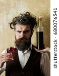 Small photo of Man posing with wine glass and bottle on female hand. Brutal hipster with long beard, moustache and messy hair on beige wall. Alcohol abuse and alcoholism. Unhealthy lifestyle. Bad habits