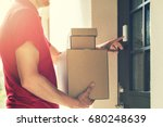 Small photo of delivery service courier ringing the house doorbell with boxes in hands