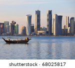Stock photo a dhow returns to harbour in doha qatar at sunset with the city s modern skyline in the 68025817