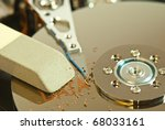 Small photo of creative view of hard disk internals with eraser symbolizing the erasure of data