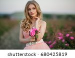 Stock photo beautiful pretty woman with long curly hair posing near pink roses in a garden 680425819