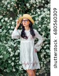 Small photo of Portrait of a Beautiful girl in a white vintage dress and straw hat standing near jasmine.Brunette romantic woman in glasses.Pretty tenderness model looking afar
