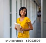A pretty Asian college student wearing yellow shirt, holding book, smiling while looking away standing inside building hallway.  Twenties female Asian Thai model of Chinese descent - stock photo