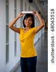 A cute playful college student wearing yellow t-shirt balancing a textbook on her head looking away. Twenties female Asian Thai model of Chinese descent - stock photo