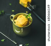 Small photo of Refreshing summer dessert. Mango sorbet ice cream scoops with fresh mint leaves in green cup over black wooden background, square crop. Clean eating, healthy, weight loss, alkaline diet food concept