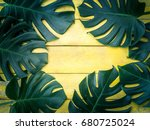green tropical leaves on yellow ... | Shutterstock . vector #680725024