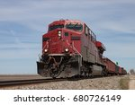 Big Red Locomotive Leading Freight Train on Canadian Prairie - stock photo