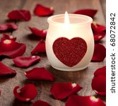 burning candle with heart and rose petals - stock photo