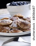 Dutch poffertjes (mini-pancakes) with fork in the forground and blueberries in the background. - stock photo
