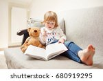 girl reading a book to teddy... | Shutterstock . vector #680919295