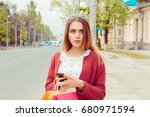 Small photo of Shocked woman with phone looking at you camera waiting for her bus at bus station seeing an accident shocked afraid isolated outdoors city near the road background. Human emotion facial expression