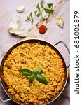 Small photo of high-angle shot of a spanish chicken paella in a paellera, the paella pan, and some ingredients to prepare it on a rustic wooden table
