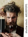 Small photo of Hipster holding bottle of wine and glass on female hand. Sad man with long beard, moustache on unhappy face and messy hair on beige wall. Alcohol abuse and alcoholism. Unhealthy lifestyle. Bad habits