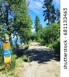 Small photo of Lake shore trail through trees with sunshine and shadows. Signs posted alongside pathway.