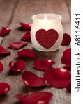 a candle with heart and rose petals for valentines day - stock photo
