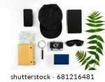 Travel accessories set on white background: smart, passport, cap, notepad, map, camera and sunglasses. Top view point.