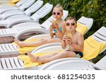 Boy and burred girl in a bathing suit and in sunglasses drink fruit cocktails with straws and look at the camera lying on white chaise lounges