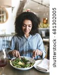 Small photo of Portrait of beautiful smiling girl with dark curly hair sitting in restaurant with glass of red wine and salad on table. Pretty African American lady eating salad at cafe