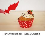 Small photo of Red bat cupcake decorated with cream and marzipan pumpkin on Halloween