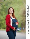 Portrait of 9 months pregnant woman on summer alley - stock photo