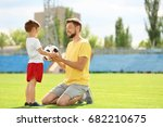 Small photo of Dad and son with soccer ball in stadium
