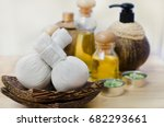 Small photo of A couple of herbal compress on wooden tray with blur background of aroma oil and aroma green flower shape candle in little silver boxes on wooden background, use for health care and spa concept