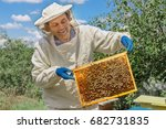 Beekeeper Holding A Honeycomb...