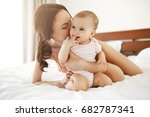 Small photo of Happy cheerful young mom smiling playing with her little baby daughter lying in bed at home.