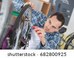 Man Inspecting The Bike Tires