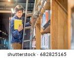 young asian man choosing book... | Shutterstock . vector #682825165