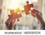 Closeup hand of woman connecting jigsaw puzzle with sunlight effect, Business solutions, success and strategy concept