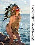 Small photo of A man with an american indian coloring and feathers on his head embraces a woman dressed in american indian style on the seashore