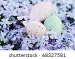 Easter eggs hidden in a bed of spring flowers. Selective focus with extreme shallow DOF. - stock photo