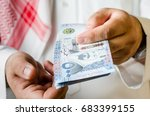 saudi man holding or paying... | Shutterstock . vector #683399155