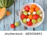 Summer fruit salad with watermelon, honeydew, cantaloupe and cheese, overhead scene on a rustic blue wood background - stock photo
