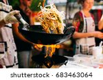 man cooks noodles on the fire | Shutterstock . vector #683463064