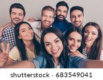 Small photo of Cheers! Funky mood. Close up of an eight excited friend`s selfie, taken by brunette girl. Young people enjoy their company, smile, have fun
