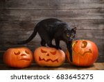 Stock photo black cat with orange halloween pumpkin on wooden background 683645275