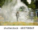 Small photo of PARIS, FRANCE - JUNE 4, 2017: Girl enjoying passing through sprinkler water circle during BiodiversiTerre event (created by Gad Weil) showing relationship of man and nature in today's society.