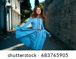 Happy woman running in a blue dress on the street