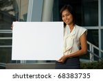 Cheerful beautiful young business woman in white blouse holding blank sign in horizontal position for custom text copy insertion outside of office building. Female dark skin Asian Thai model - stock photo