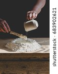 Small photo of Senior woman kneads pastry, pouring water from mug to flour. Vertical crop, subdued colors, details on old working hands and food ingredients